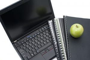 Computer education and learning concept with an open laptop lying beside a set of sprial bound notebooks topped with a healthy green apple
